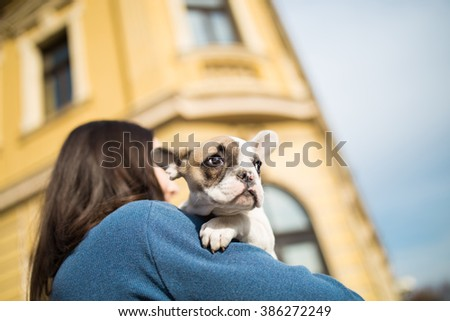 Young casually dressed woman holding her adorable French bulldog puppy. Close up shot with wide angle lens. Old, rustic building in background.