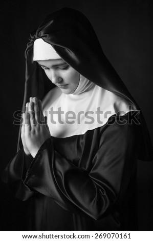 Young catholic nun with pray. black and white photo. - stock photo