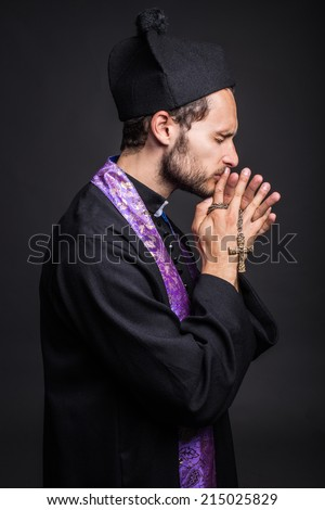 Young catholic priest praying. Studio portrait on black background   - stock photo