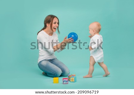 Young Caucasian attractive smiling mother playing with her cute little son with a ball and colored blocks, baby boy wearing bodysuit running isolated on blue - stock photo
