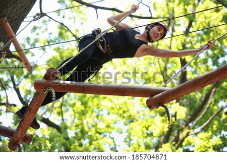 Young caucasian attractive woman climbing in adventure rope park in mountain helmet and safety equipment  - stock photo