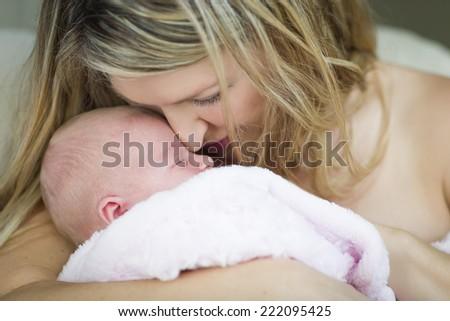 Young Caucasian Beautiful Mother Holding Her Precious Newborn Baby Girl. - stock photo