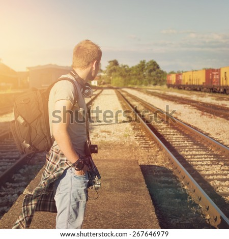 Young Caucasian blond hipster man with backpack waiting for train at a station. Trendy casual guy standing looking away, unrecognizable person, square format image, filter applied. - stock photo