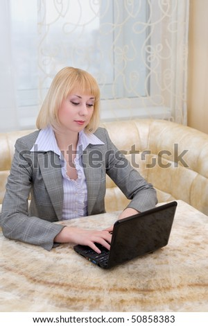 young caucasian blonde businesswoman works at laptop - stock photo