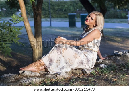 Young Caucasian blonde woman is posing outdoors near stone wall.