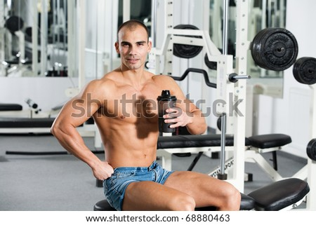 young caucasian bodybuilder in the gym, holding a protein shake - stock photo