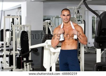 young caucasian bodybuilder in the gym smiling, with a towel around his neck - stock photo