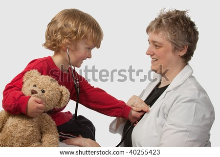 Young caucasian boy and a short hair woman in medical doctor uniform holding a stethoscope on his ear listening to doctor heart beat holding a brown teddy bear