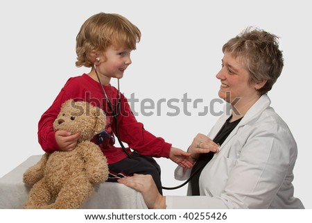 Young caucasian boy and a short hair woman in medical doctor uniform holding a stethoscope on his ear listening to doctor heart beat holding a brown teddy bear - stock photo