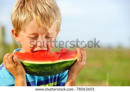 Young caucasian boy bites into his juicy watermelon - stock photo