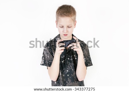 Young caucasian boy browsing snapshots or video on a smart phone isolated on white background.