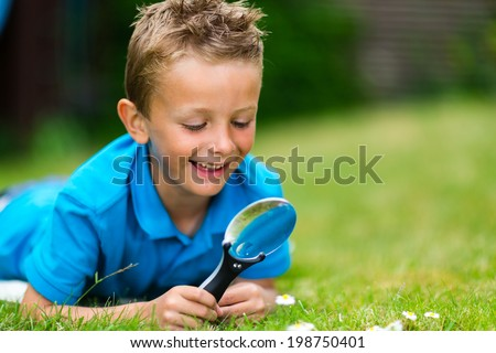 Young caucasian boy exploring garden during summer time with his magnifier. - stock photo