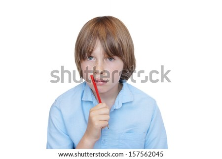 Young Caucasian boy looking stressed or worried with pencil in hand, homework or school related - stock photo