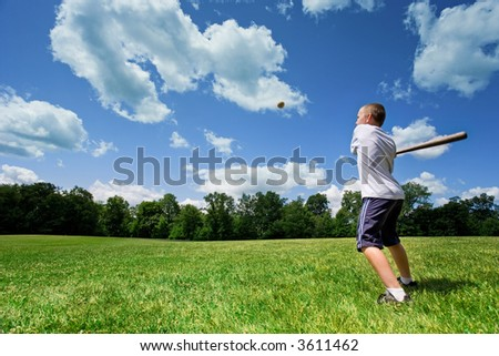 Young Caucasian boy playing baseball in a sunny field on a beautiful summer day.