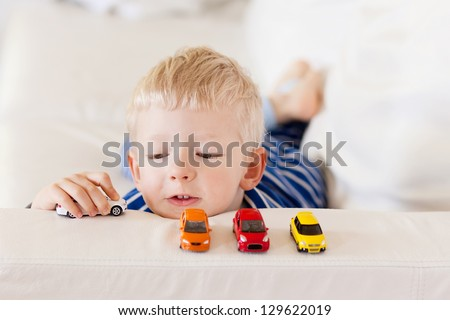 young caucasian boy plays with colorful toy cars - stock photo
