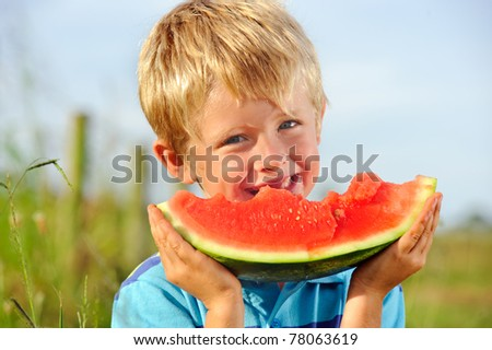 Young caucasian boy smiles with his half eater watermelon - stock photo
