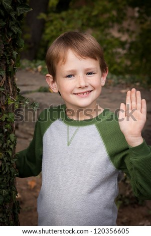 Young Caucasian boy standing next to a tree with green ivy waving - stock photo