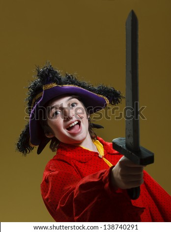Young caucasian Boy with large purple pirate hat, red shirt and gray sword. Boy holds sword in the air yelling happily. - stock photo