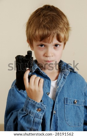 Young Caucasian  boy with toy gun in blue shirt - stock photo
