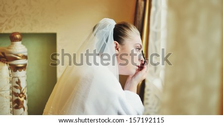 young caucasian bride having make up in the morning.