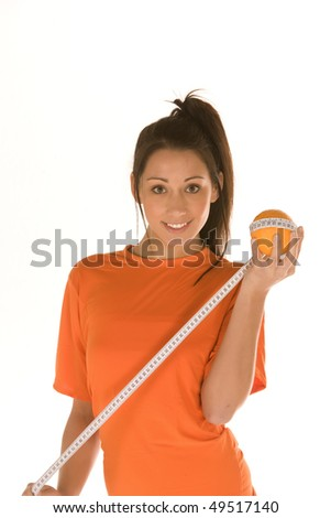 young caucasian brunette holds an orange and wrap around it a measuring tool