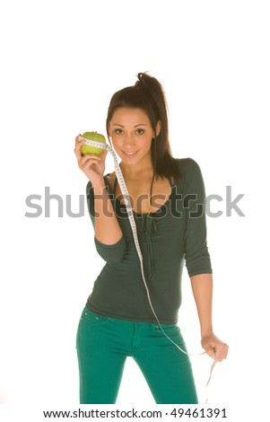 young caucasian brunette isolated on white holds a granny smith apple and a measuring tool