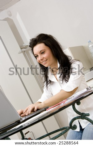young caucasian brunette with a laptop at home smiling