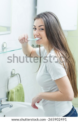 Young Caucasian Brunette Woman Brushing Teeth in the bathroom. - stock photo