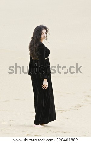 Young caucasian brunette woman in black dress looking over shoulder while standing on sand