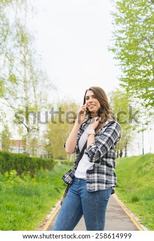 Young Caucasian brunette woman speaking on smartphone outdoors in spring. Casual teenage girl in park standing talking on the phone. Vertical, very mild retouch, natural light and colors, no filter. - stock photo
