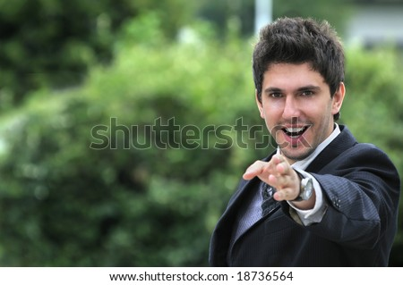 Young caucasian business man in a suite, pointing at camera to you - stock photo
