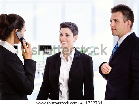 Young caucasian business people meeting at bright office. Smiling, copyspace, suit. - stock photo