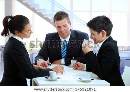 Young caucasian business people meeting at office table, drinking coffee. Suit and tie, sitting, smiling, looking at papers. - stock photo