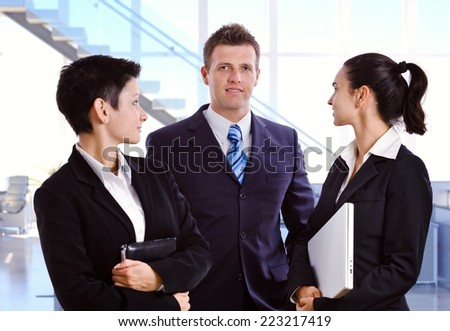 Young caucasian business team at bright office, businesswoman looking at businessman in background. Suit and tie, looking at camera, standing. - stock photo