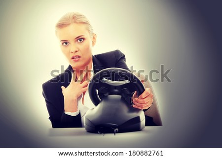 Young caucasian business woman playing on computer (with steering wheel) - stock photo