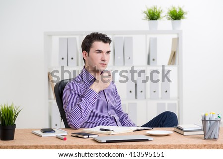 Young caucasian businessman drinking coffee at his workplace in office - stock photo