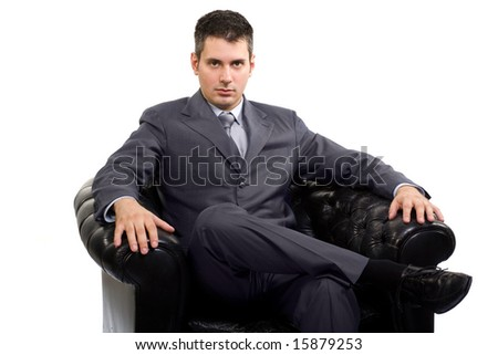 Young caucasian businessman in a suite, sitting in armchair - stock photo