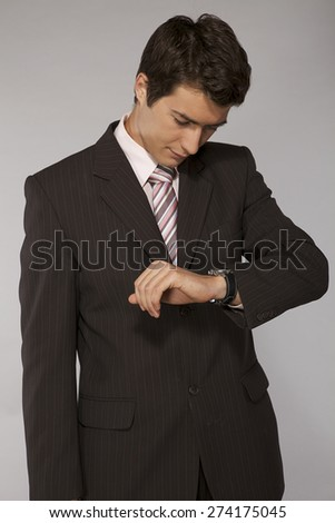 Young caucasian businessman looking on his watch - stock photo
