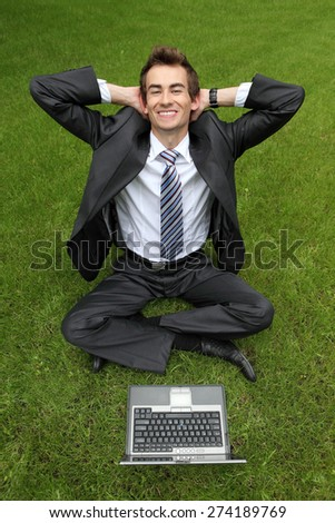 young caucasian businessman relaxing on grass with his laptop - stock photo