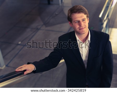 Young Caucasian businessman using escalator and looking up