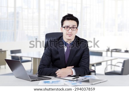 Young caucasian businessman with formal suit, sitting and smiling in the office with laptop computer and document on the table - stock photo