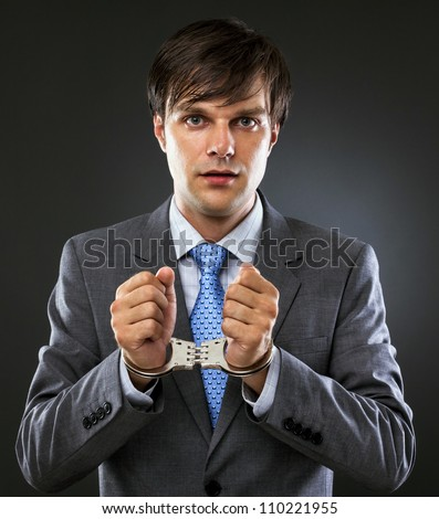 Young caucasian businessman with handcuffed hands . Studio shot. Gray background - stock photo