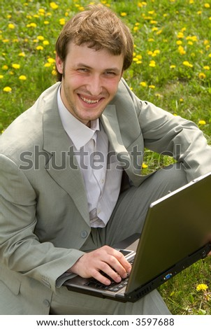 Young caucasian businessman with laptop on green grass background
