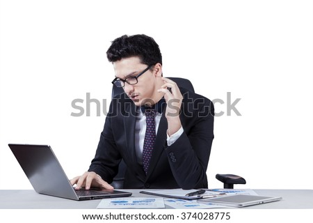 Young caucasian businessperson working on desk with financial document on desk while typing on the laptop computer, isolated on white background - stock photo