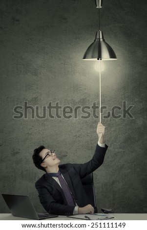Young caucasian businessperson working on desk with laptop and pulling a lightbulb, symbolizing discover idea - stock photo