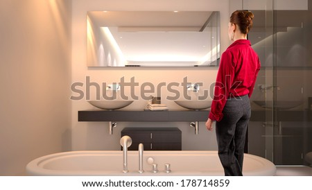 young Caucasian businesswoman, tourist, or relator in a hotel bathroom - stock photo