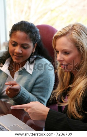 Young caucasian businesswoman with coworkers in an office setting - stock photo
