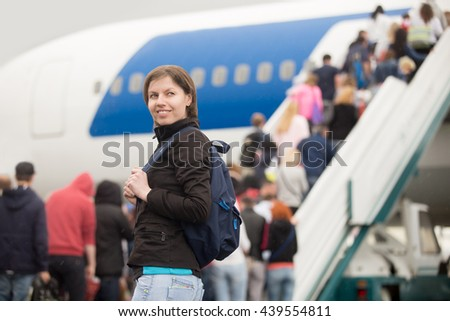 Young Caucasian cheerful smiling woman passenger in 20s travelling with backpack, boarding airplane, people climbing ramp on background - stock photo