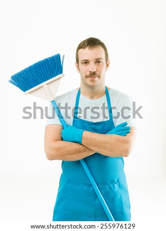 young caucasian cleaner holding broom with arms crossed, standing against white background - stock photo