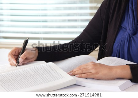 Young caucasian college girl is doing her homework and preparing for her examination. She is seated at a desk by the window in a library. Shot in the studio with DSLR - stock photo
